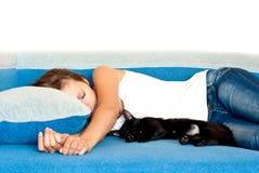 Menina e um gato que dorme ao lado das posições similares Foto de Stock Royalty Free