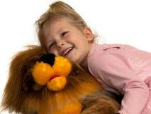 Menina e um leão do brinquedo Imagem de Stock Royalty Free
