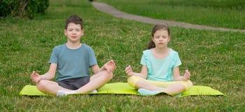 a menina e um menino sentam-se em um tapete da ioga e meditam-se, fora imagens de stock