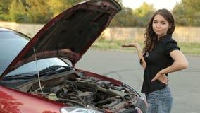 Menina e um vermelho quebrado do carro na estrada filme