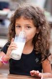 Menina e vidro do leite fotografia de stock