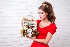 A menina elegante bonita em um vestido vermelho longo e em sapatas guarda um bir Foto de Stock Royalty Free