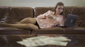 Menina elegante bonita que encontra-se no funcionamento de couro do sofá com o portátil no fundo, guardando um pacote de dólares video estoque