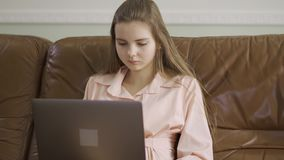 Menina elegante bonita que senta-se no sofá de couro que datilografa no teclado do portátil que mostra então o sinal APROVADO com vídeos de arquivo