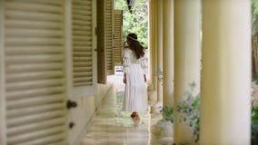 A menina elegante em um vestido longo branco anda entre as colunas brancas filme