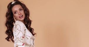 Menina elegante feliz no vestido branco que joga com cabelo longo video estoque