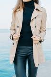 Menina elegante magro em um revestimento bege e em umas calças pretas no CCB do mar fotografia de stock royalty free