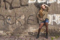 Menina elegante nova que levanta perto da parede velha imagem de stock