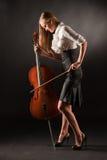 Menina elegante que joga com paixão no baixo-viol foto de stock