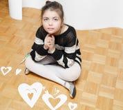 a menina elegante que senta-se e que sonha no assoalho de folhosa com corações de papel cortou para o dia de Valentim Imagem de Stock Royalty Free