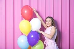 Menina elegante que toca em balões coloridos na parede cor-de-rosa do metal fotos de stock royalty free