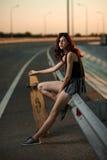 Menina elegante urbana com o longboard que levanta fora na estrada no por do sol Imagem de Stock Royalty Free