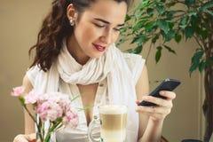 A menina elegante verifica suas redes sociais no telefone celular no Ca Fotografia de Stock