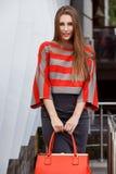 A menina elegante vestida em uma saia cinzenta, em uma blusa vermelha e cinzenta listrada guardando um saco vermelho levanta na r fotos de stock