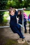 Menina elementar feliz da escola da idade no campo de jogos Imagem de Stock Royalty Free