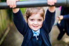 Menina elementar feliz da escola da idade no campo de jogos Foto de Stock