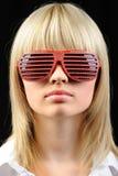 A menina em óculos de sol à moda - jalousie fotografia de stock royalty free