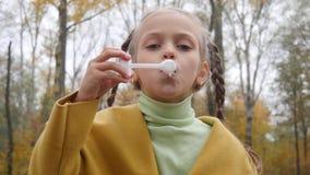Menina em bolhas de ar de sopro do revestimento amarelo no parque em um dia nebuloso filme