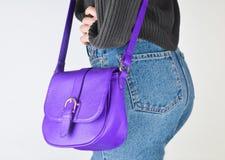 Menina em calças de brim do ajuste, camiseta e com o saco no levantamento das probabilidades foto de stock