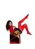Menina em calças justas vermelhas em uma caixa com um presente fotos de stock royalty free