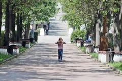 A menina em camiseta listrada mostra a língua e está entre árvores Fotografia de Stock Royalty Free