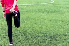 A menina em caneleiras pretas dos esportes e em um revestimento cor-de-rosa amassa antes de treinar em uma arena esportiva aberta fotografia de stock royalty free