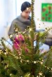 Menina em casa ao decorar a árvore de Natal Imagens de Stock Royalty Free