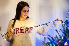 Menina em casa ao decorar a árvore de Natal Fotos de Stock