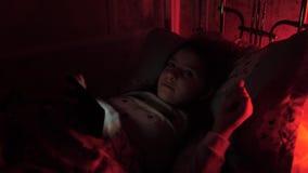 Menina em casa na noite que olha algo no smartphone vídeos de arquivo