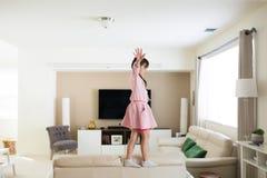 Menina em casa sobre a mobília imagem de stock