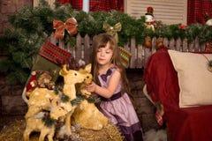 A menina em decorações do ` um s do ano novo aproxima a rena do brinquedo Fotografia de Stock Royalty Free