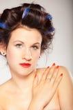 Menina em encrespadores de cabelo no cinza Imagens de Stock