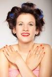 Menina em encrespadores de cabelo no cinza Fotografia de Stock Royalty Free