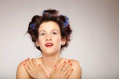 Menina em encrespadores de cabelo no cinza Imagem de Stock
