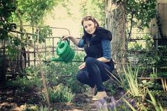 Menina em flores de jardinagem das águas Fotografia de Stock