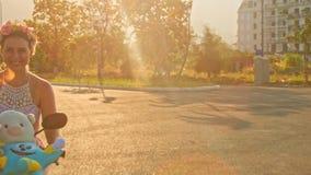 Menina em Garland Rides Moped sob a luz solar brilhante video estoque