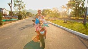 A menina em Garland Speeds na bicicleta motorizada passa plantas tropicais video estoque