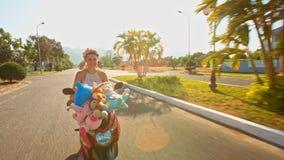 Menina em Garland Speeds no velomotor ao longo de City Road filme