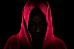 Menina em Hood Making Scary Wolf Face vermelho fotos de stock royalty free