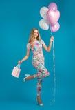 Menina em macacões da mola com balões, humor despreocupado Fotografia de Stock Royalty Free
