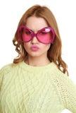 A menina em monóculos cor-de-rosa grandes dos corações dá forma, calças de brim vestidas e uma camiseta verde que levanta no estú Imagem de Stock Royalty Free