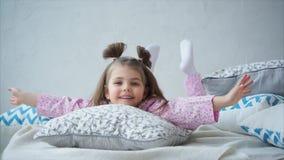 Menina em pijamas bonitos na cama e pensativamente em agitar seus pés vídeos de arquivo