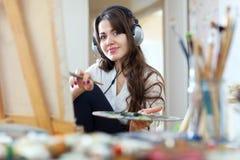 Menina em pinturas dos fones de ouvido com cores de óleo Imagens de Stock Royalty Free