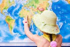 Menina em pontos de um chapéu a um mapa do mundo com um dedo fotos de stock