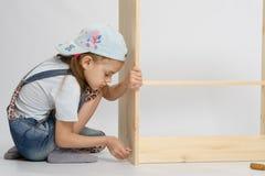 Menina em rotações do parafuso da mobília do coletor dos macacões Foto de Stock