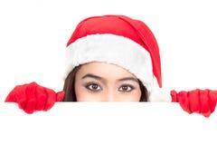 Menina em Santa que espreita sobre a placa do sinal Fotografia de Stock Royalty Free