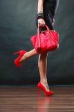 A menina em sapatas cravadas vermelhas do vestido curto preto guarda a bolsa Fotos de Stock Royalty Free