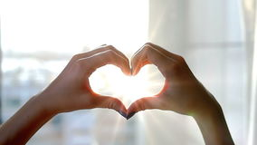 A menina em seu quarto na janela trava suas mãos, feitas sob a forma de um coração, os raios do ` s do sol Bokeh filme