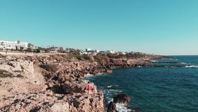 Menina em suportes vermelhos do vestido em penhascos rochosos com os braços aos lados Ondas fortes brancas do mar que batem o lit vídeos de arquivo