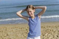 Menina em t-shirt listrado que olha o mar imagem de stock